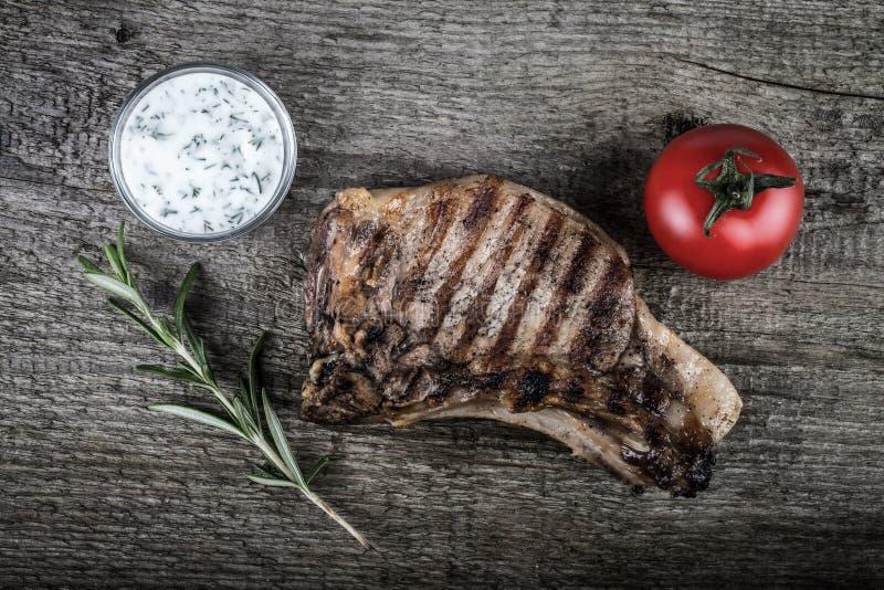 Viande grillée chaude avec des légumes et marinade de vinaigre crémeuse sur le vieux conseil en bois gris photo stock