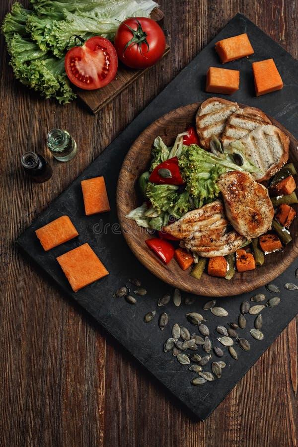 Viande grillée délicieuse assortie avec les légumes frais au-dessus du fond en bois foncé image stock