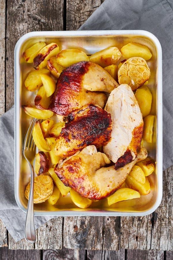 Viande grillée de poulet, jambe, cuisse avec les pommes de terre cuites au four, ail Vue verticale et supérieure Vieille table en photo libre de droits