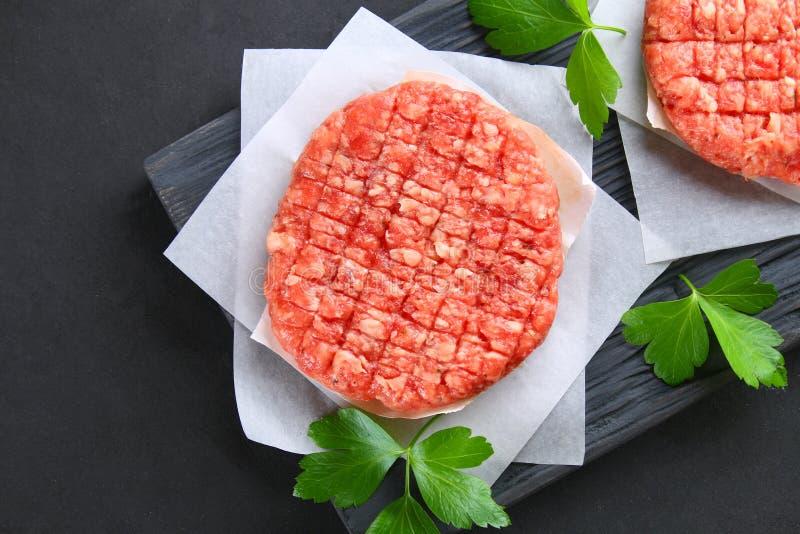 Viande hachée crue pour les hamburgers faits à la maison de gril faisant cuire avec les espaces et des herbes photos libres de droits
