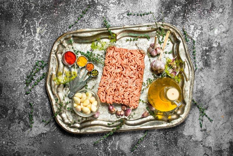 Viande hachée fraîche avec des épices et des herbes sur un plateau en acier photo libre de droits
