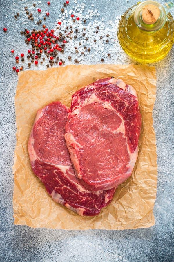 Viande marbr?e organique fra?che crue Boeuf, sel de mer, poivre et ail sur la table Noir Angus de Ribeye de bifteck d'oeil de ner photo stock