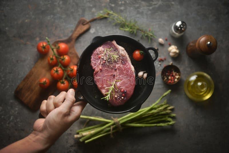Viande marinée crue dans la casserole de fer en main, et ingrédients entourant sur le fond inférieur Vue d'en haut, image horizon photo stock