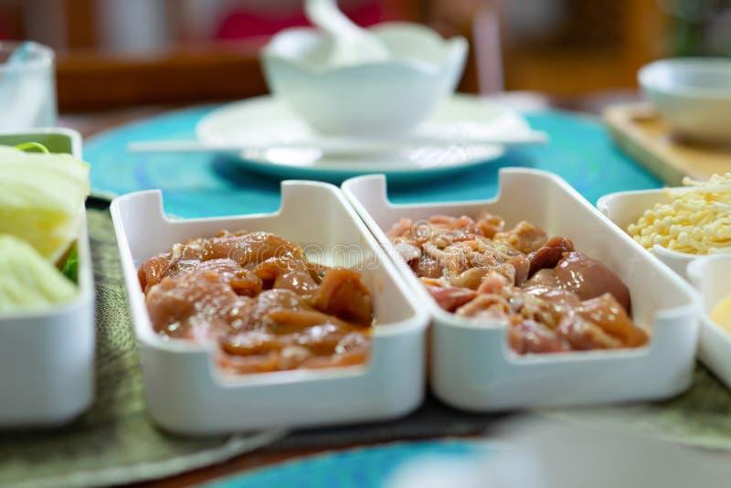 Viande marin?e de poulet et porc marin? sur un plateau en plastique blanc dans un ensemble japonais de shabu-shabu images stock