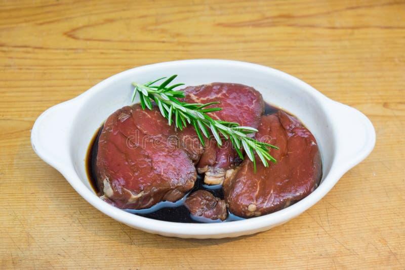 Viande marinant : Filet d'oeil de bifteck de boeuf dans le plat blanc du sauc de soja photo stock