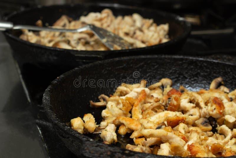Viande rôtie avec des champignons dans une casserole de laquelle la vapeur vient, plan rapproché, fond photos stock