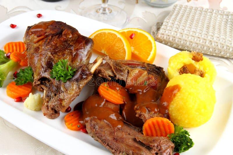 Viande sauvage cuite au four de lapin avec des boulettes et des légumes de pomme de terre photo stock