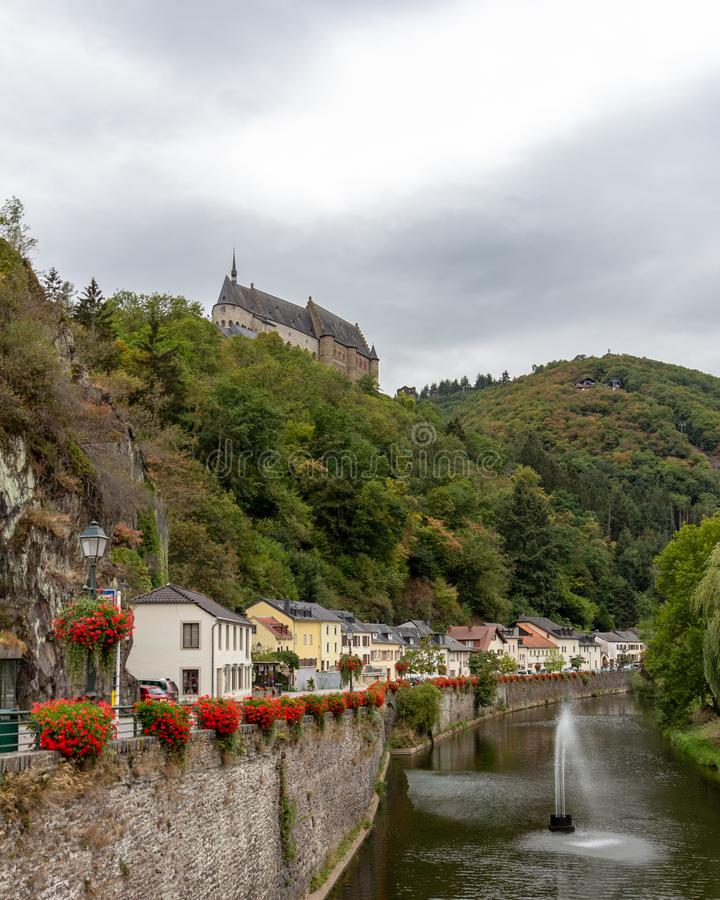 Vianden Castle above the village in Luxembourg. View of Vianden Castle from the Our River, perched atop a hill above the village of Vianden, Luxembourg stock photo