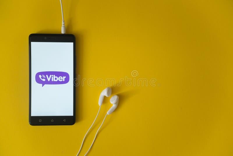 Viberembleem op het smartphonescherm op gele achtergrond royalty-vrije stock afbeeldingen