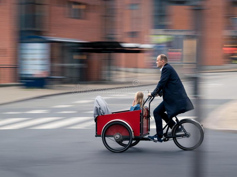VIBORG, DENMARK - SEPTEMBER 21, 2016: An unidentified man riding a cargo bike stock image