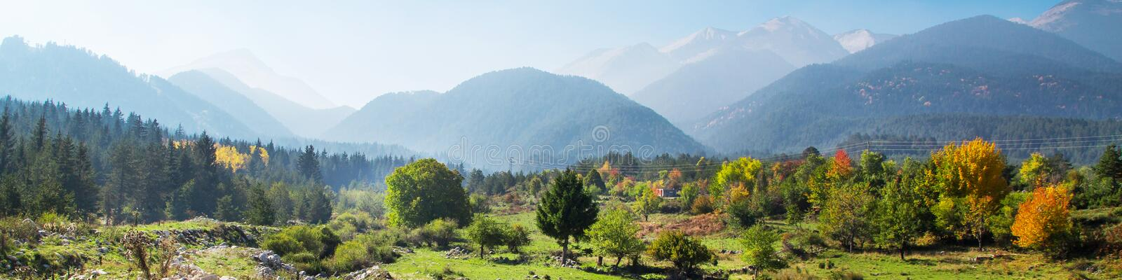 Vibrant autumn panorama background with colorful green, red, yellow trees and mountains peaks royalty free stock photography