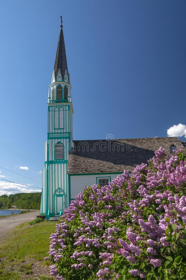 Turquoise and white church: Our Lady of Good Hope. With vibrant blooming lilac in the foreground, the unique/y painted church of Our Lady of Good Hope in Fort St stock images