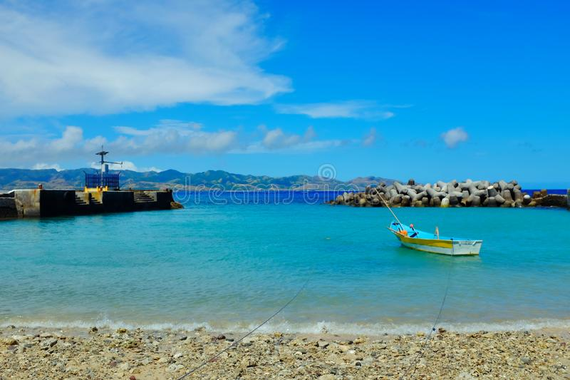 Vibrant blue tropical travel summer destination in the Philippines. Vibrant blue tropical travel summer destination. A boat docked on a local seaport in Batanes stock images