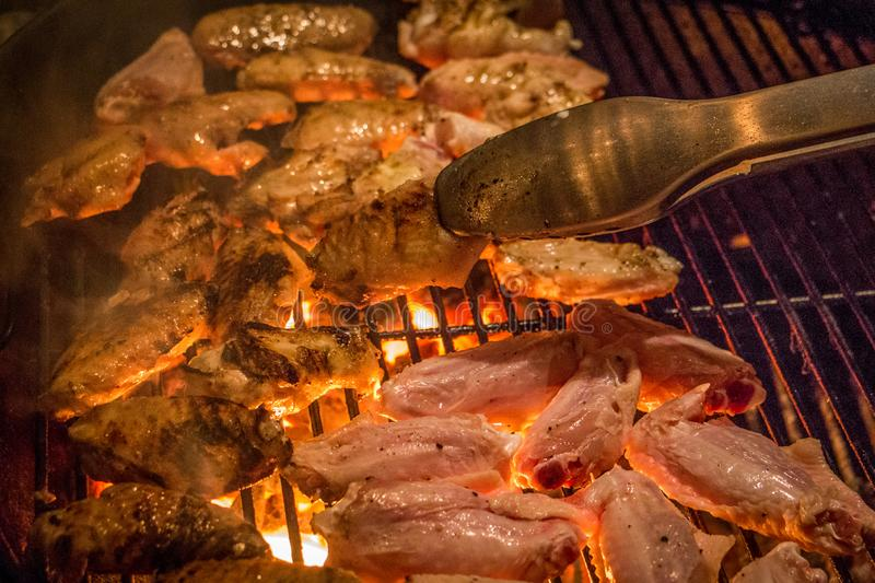 Grilled Chicken Wings on a Barbecue. Vibrant, Close Up Photo of Grilled Chicken Wings Cooking on a Barbeque - Turning Over Raw Wings with a Pair of Tongs Onto stock images
