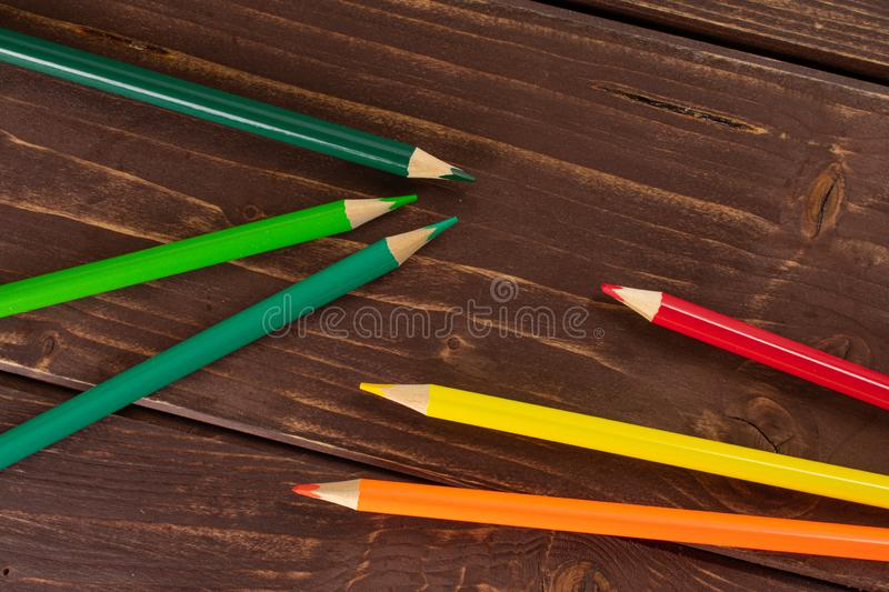 Vibrant colored pencil on brown wood. Group of six whole colored pencil flatlay on brown wood stock photo