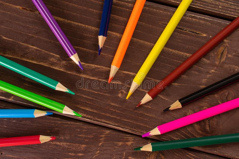 Vibrant colored pencil on brown wood. Group of twelve whole colored pencil flatlay on brown wood stock image