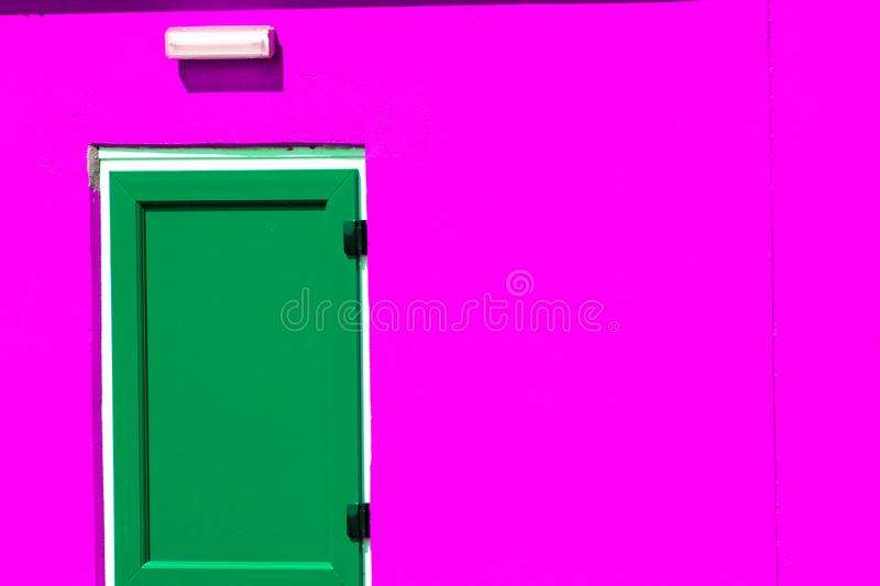 Vibrant colorful paint. Green painted door on neon pink building. Vibrant colorful paint. Green painted door on striking neon pink building exterior. Bright stock photo