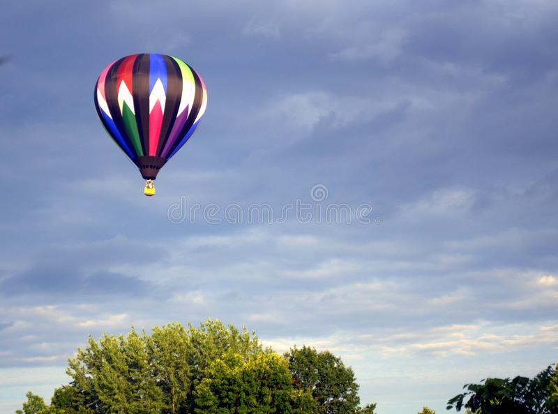 Vibrant Colorful Piloted Helium Hot-Air Balloon in Flight. Vibrantly colored helium hot-aired balloon in flight. Red, blue, green, violet, pink, are among the stock photos