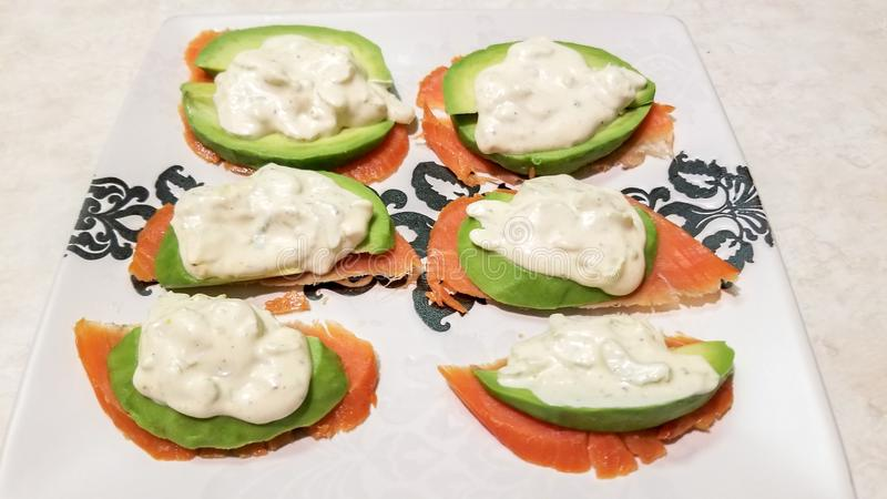 Vibrant, colorful pink cold smoked salmon lox slices topped with green avocado and remoulade sauce, on top of a white ceramic plat royalty free stock photography