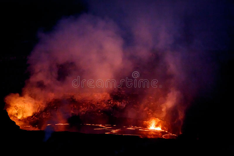 Vibrant colors, reds, pinks and yellows surround crater of active volcano glowing in the nighttime sky. Vibrant reds, pinks and yellows surround crater of active stock photo