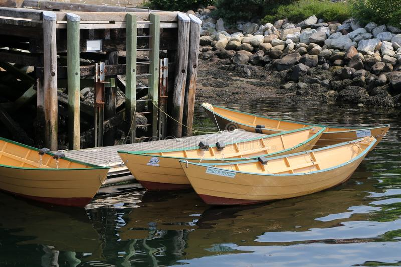 The 3 small rowboats are tied to the pier. stock images