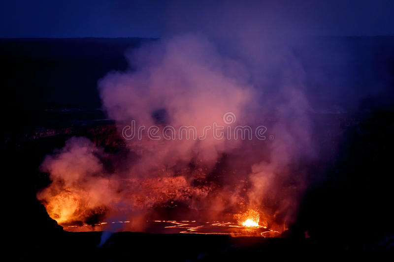 A Vibrant array of colors surround crater of active volcano glowing in the nighttime sky. Vibrant colors surround crater of active volcano glowing in the stock image
