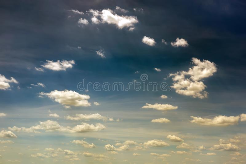 Vibrant dark blue sky with white to yellow clouds. Beautiful moody nature background royalty free stock photo