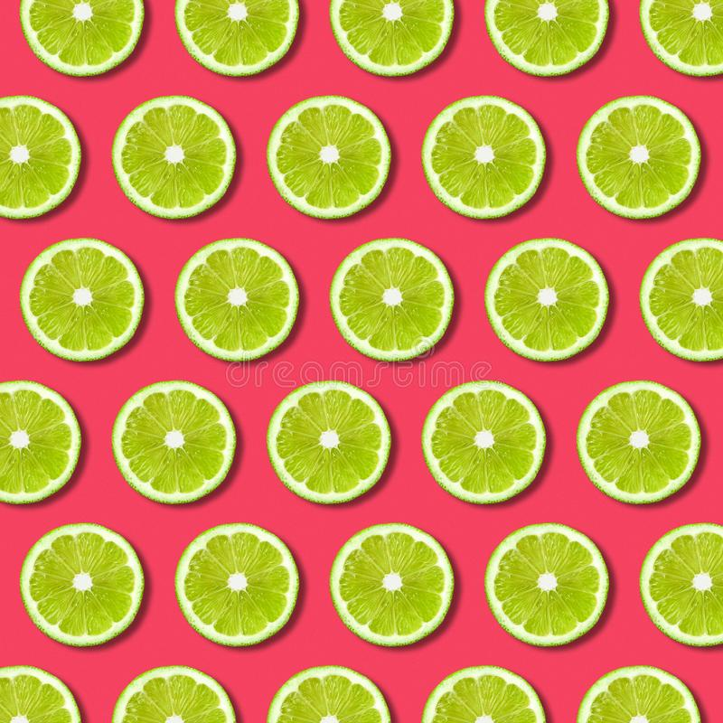 Vibrant fruit pop art background with green lime slices on red background stock image