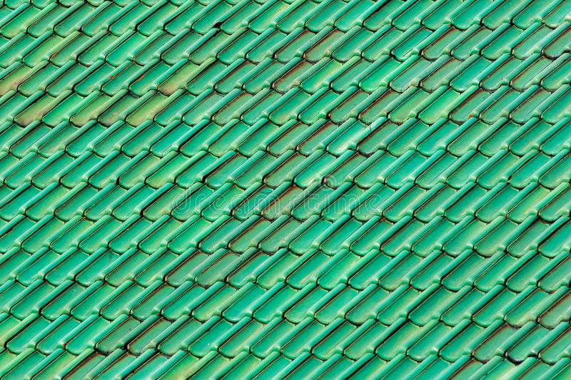 Vibrant green roof tiles. Patterned and textured background image of colored tiles stock image