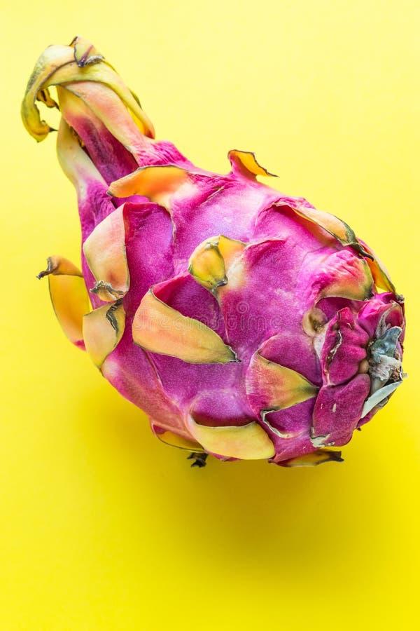 Whole dragon fruit pitaya close-up on yellow background royalty free stock images
