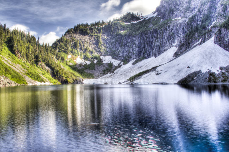 Vibrant Lake. Lake Serene in Washington. The vibrant colors of the green grass contrast with the snowy cliffs stock photos