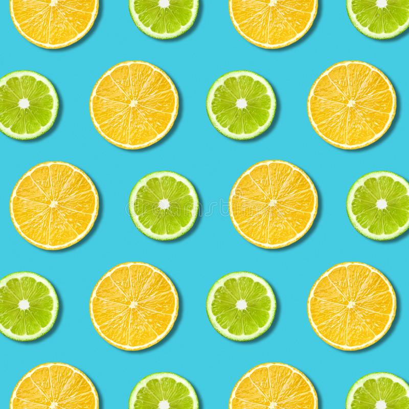 Vibrant lemon and green lime slices texture on turquoise background royalty free stock photos