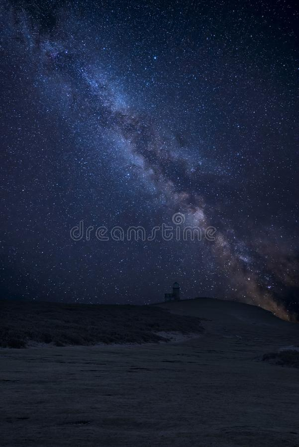 Vibrant Milky Way composite image over landscape of Belle Tout lighthouse on South Downs National Park royalty free stock photography