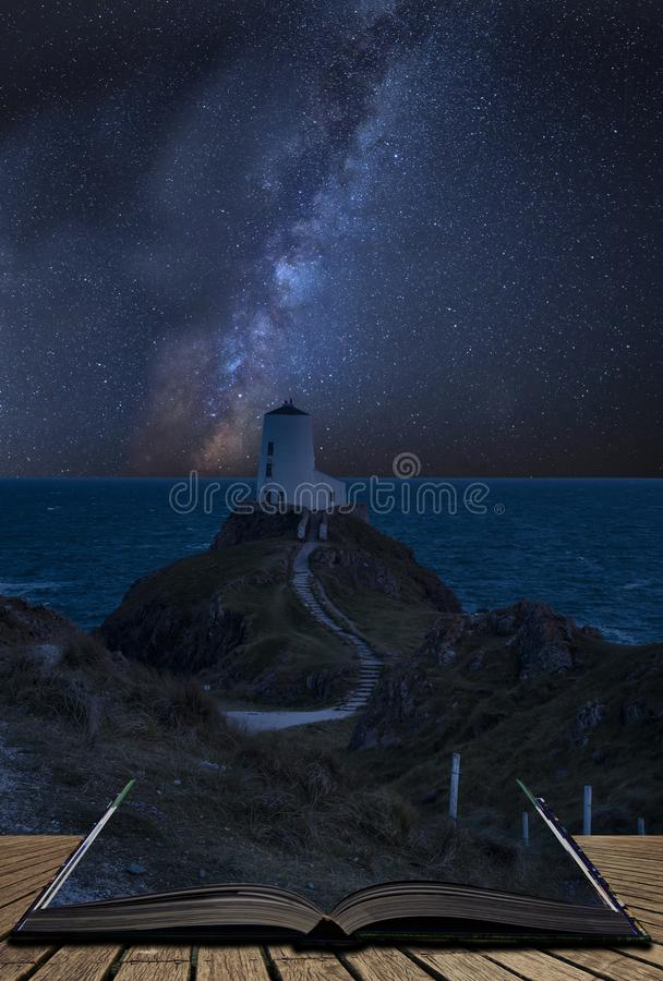 Vibrant Milky Way composite image over landscape of lighthouse on end of headland with beautiful sky coming out of pages in stock photography