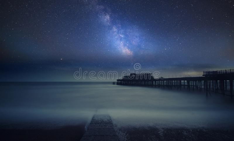Vibrant Milky Way composite image over landscape of Long exposure of ruined pier at sea royalty free stock images