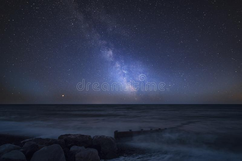 Vibrant Milky Way composite image over landscape of pier at sea stock images