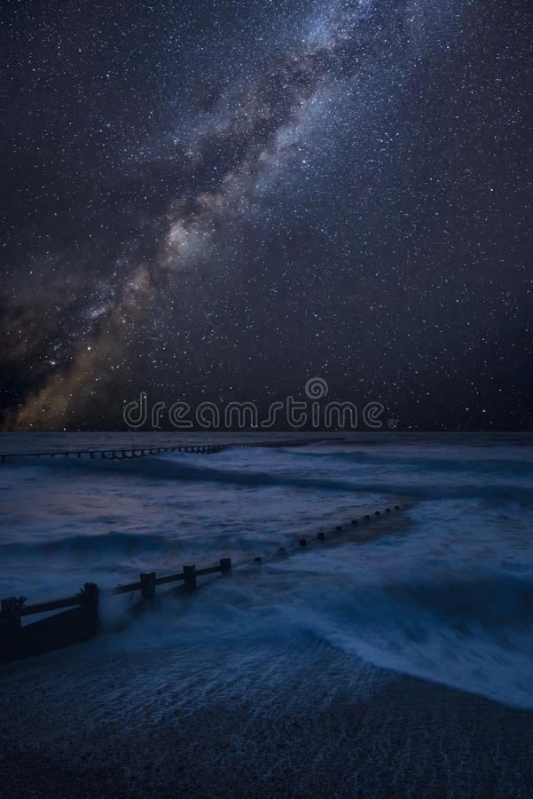 Vibrant Milky Way composite image over landscape of waves crashing onto beach royalty free stock images