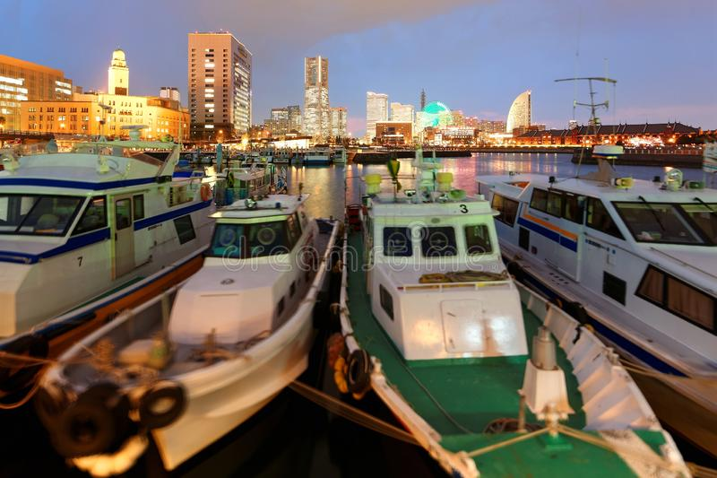 Vibrant night scenery of Yokohama Minatomirai Bay Area with boats and ships parking in the marina. Colorful lights of a giant Ferris wheel and Landmark Tower royalty free stock photography