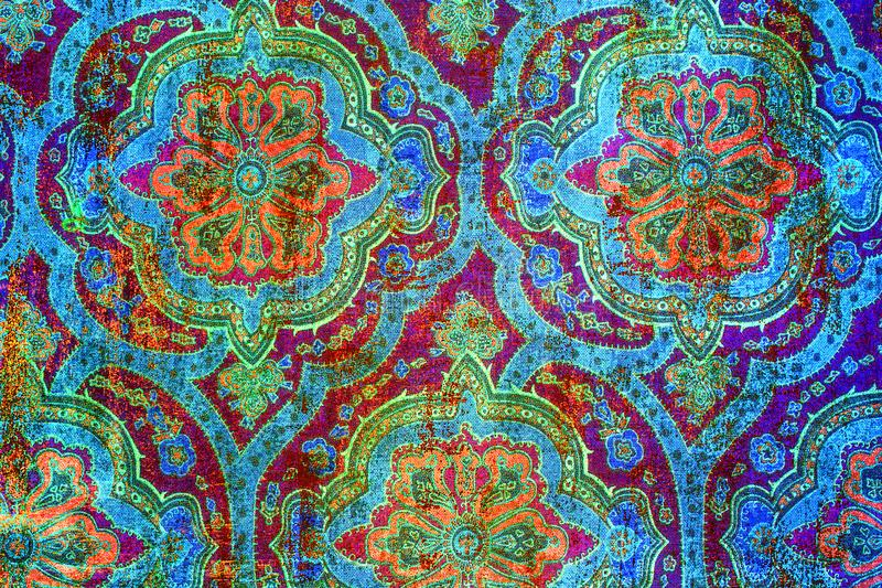 Vibrant old fashioned shabby paper pattern. A closeup of an old fashioned shabby colourful repeating flower pattern printed on paper background stock image