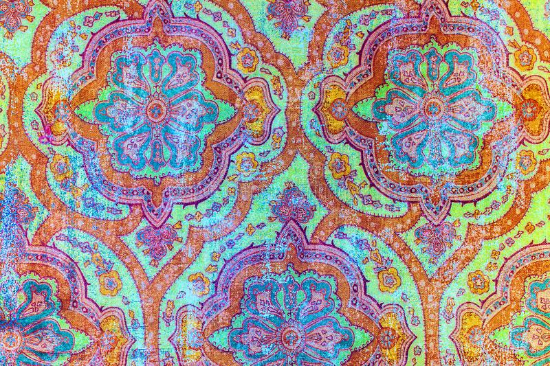 Vibrant old fashioned shabby paper pattern. A closeup of an old fashioned shabby colourful repeating flower pattern printed on paper background royalty free stock photos