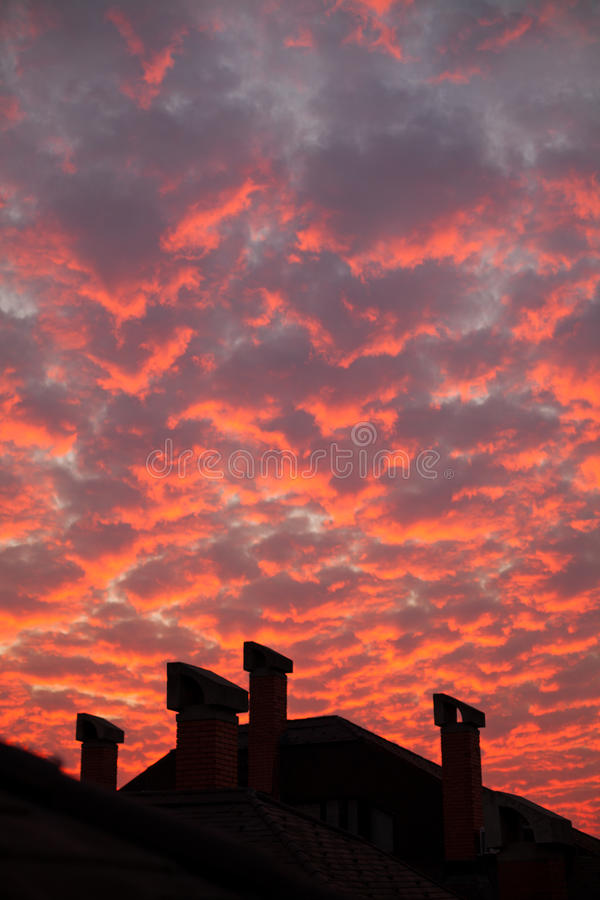 Vibrant orange clouds over rooftop chimneys stock photo