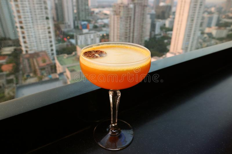 Vibrant orange cocktail on the rooftop bar`s black table with aerial urban view in the backdrop stock images