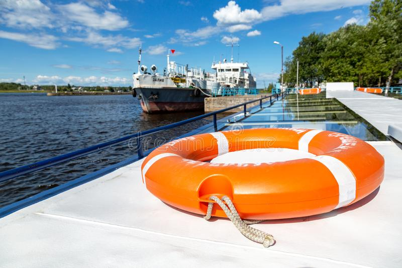 Vibrant orange lifebuoy on the excursion boat in summer day. Saint Petersburg, Russia - August 8, 2018: Vibrant orange lifebuoy on the excursion boat in summer stock image