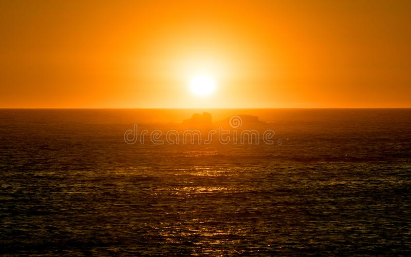 Vibrant orange sunset on the ocean with reflections on water surface and rocks in silhouette royalty free stock images