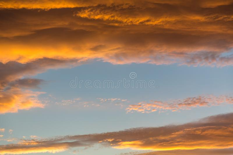 Vibrant orange and yellow sunset sky. With large covering of cumulus clouds stock photo