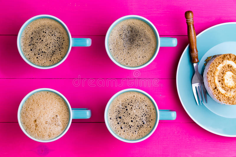 Vibrant overhead image of coffee and cake. With four aligned blue cups of frothy black espresso coffee with their handles pointing to chocolate swiss roll cake royalty free stock image