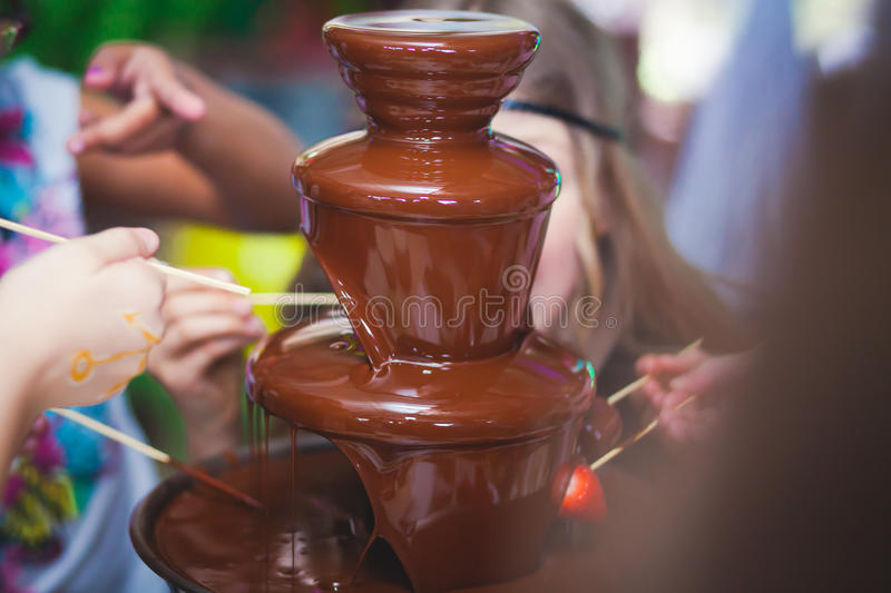 Vibrant Picture of Chocolate Fountain Fontain on childen kids birthday party with a kids playing around and marshmallows and fruit. S dip dipping into fountain stock photos