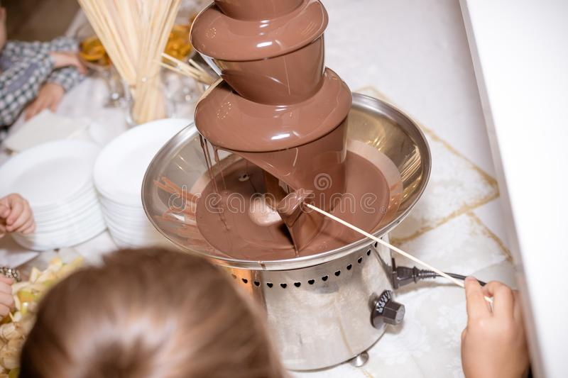 Chocolate Fountain on kids birthday party with a kids playing around and marshmallows and fruits dip dipping into stock images