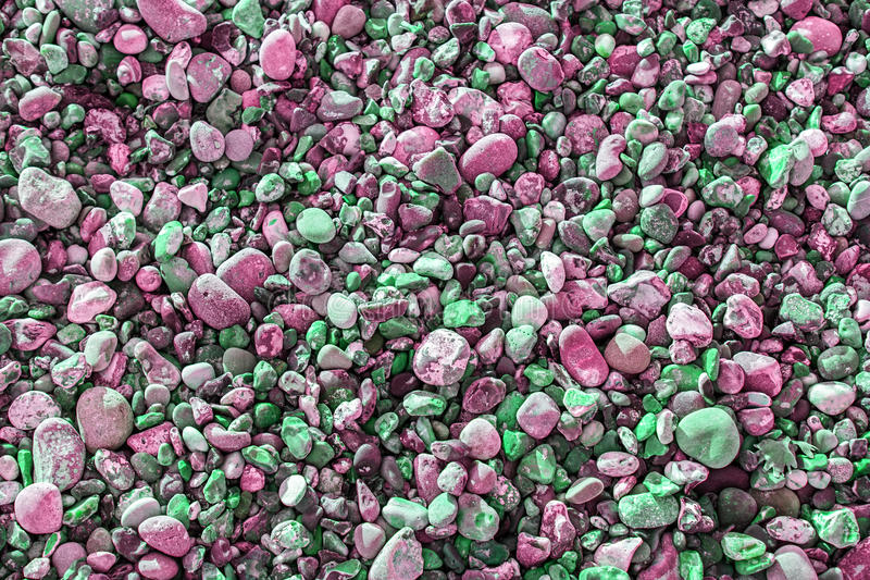 Vibrant pink and green pebbles. And gravel forming a colorful abstract background texture royalty free stock photos