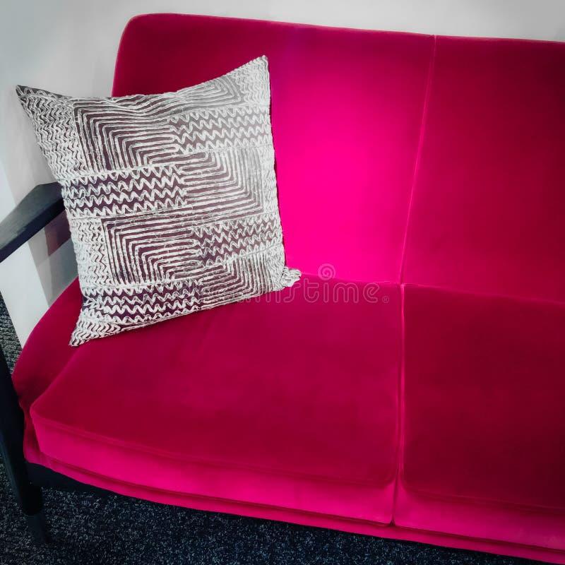 Vibrant pink velvet sofa with ornamental cushion. Luxurious furniture stock photos